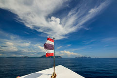 Thailand flag with boat sails to Koh Phi Phi island, Thailand Stock Image