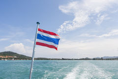 Thailand flag with boat wake at Koh Pha Ngan island Royalty Free Stock Photos