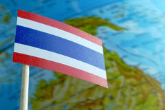 Thailand flag with a globe map as a background. Macro royalty free stock photography
