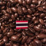 A Thailand flag placed over roasted coffee beans stock photo