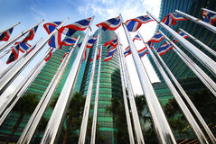 Thailand Flag poles. In front of office, against daily blue sky and green glass buildings Stock Images