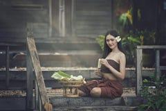 Thailand-Frau im Trachtenkleid, das für gemacht von den Blumengirlanden sitzt stockfotos