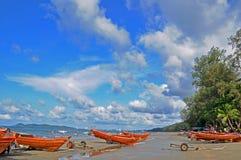 Thailand: Hav och blå himmel, vitt moln och färgrika fiskebåtar arkivbilder
