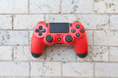 THAILAND - JAN 5: the new sony dualshock 4. Red color controller for PlayStation 4 taken in BANGKOK THAILAND on 5 JAN 2016 Stock Photos