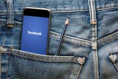 THAILAND - 13 JULI - Facebook för massmedia för Smartphone öppning social applikation på skärmen, i jenimjeanfack med blyertspenn Arkivfoton