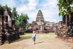Thailand Juni 1st, 2011 Turisten för den unga kvinnan som tycker om en sikt av den gamla templet Prasat Hin Phimai, på historiska arkivbilder