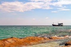 Thailand Koh Samet Old Style Ship near Rocky shore. Beneath Clouds Stock Photo