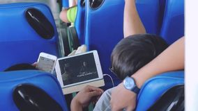 Thailand, Koh Samui, 21 december 2015. Asian couple traveling on a ship, relaxing watching a movie on a tablet and using. Couple traveling on a ship, relaxing stock video footage