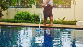 Thailand, Koh Samui, 2 december 2015. Worker man clean a swimming pool in resort. Stock Images