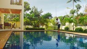 Thailand, Koh Samui, 2 december 2015. Worker man clean a swimming pool in resort. Royalty Free Stock Photos