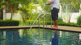 Thailand, Koh Samui, 2 december 2015. Worker man clean a swimming pool in resort. Royalty Free Stock Photo