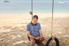 The man is sitting on a swing and listening to music. Lifestyle concept. Thailand, Krabi. February 2017. Thailand, Krabi. February 2017. The man is sitting on a Royalty Free Stock Photos