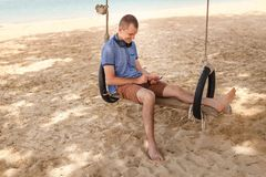 The man is sitting on a swing and listening to music. Lifestyle concept. Thailand, Krabi. February 2017. Thailand, Krabi. February 2017. The man is sitting on a Stock Photography