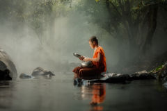 Thailand litet munksammanträde på The Creek eller floden i skog på royaltyfria bilder