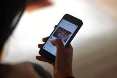 Women like a photo on Instagram application on smartphone stock photos