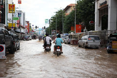 Thailand Monsoon , People on motorcycle. Drive through flooded street Stock Photos