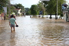 Thailand Monsoon People walking through flooded  Stock Photography