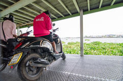Thailand : Motorcycle riders parked on ships waiting to cross to the other side of the river. Stock Photos