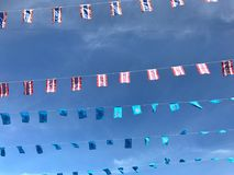 Thailand national flags and Her Majesty Queen Sirikit in blue ones. Hanging on strings with blue sky as background Royalty Free Stock Photography