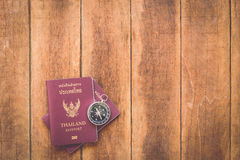 Thailand passport and compass on wood Royalty Free Stock Photo