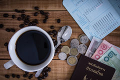 Thailand Passport with currency , Coffee and Glasses on a Wood B Stock Photo