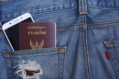Thailand Passport in denim jeans pocket and smartphone Stock Photos