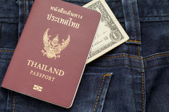Thailand passport and dollar cash puting on blue jean pants,this image for fashion and travel. Thailand passport and one dollar cash puting on blue jean pants royalty free stock photography