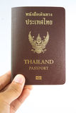 Thailand Passport. In human hand isolated on white background stock images