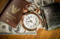 Thailand passport. Laying atop a pile of American dollars.Clock , wallet royalty free stock photos