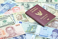 Thailand passport on mixed currency banknotes. Represent international travelling stock photography