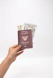Thailand passport, money in female hand. On white background royalty free stock photo
