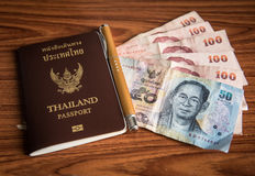 Thailand passport and money. With thai currency on wood table royalty free stock photo