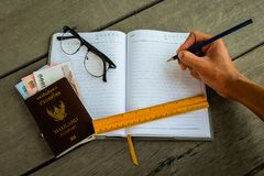 Thailand passport with money, yellow ruler, hand with pencil. Writing on notebook and glasses - concept prepare to travel royalty free stock photography