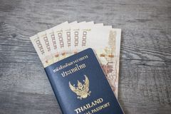 Thailand Passport and pile of Thai bath money passport Stock Photo