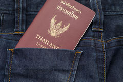 Thailand passport puting on blue jean pants,this image for fashion. And travel royalty free stock photo