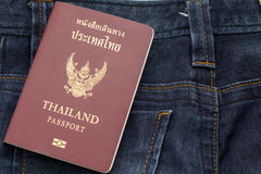 Thailand passport puting on blue jean pants,this image for fashion. And travel royalty free stock photography