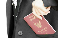 Thailand passport in suit. Hand holding thailand passport in pocket of black suit royalty free stock photo