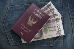 Thailand passport and Thai money in jeans pocket Royalty Free Stock Image