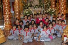 Thailand Phuket, 01 18 2013 Grundskolastudenter och en lärare i Buddhatemplet, gruppfoto Utbildning utbildning royaltyfria bilder