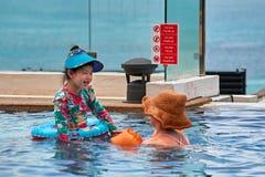 THAILAND, PHUKET, am 20. März 2018 - chinesische Mutter und nette kleine Tochter schwimmen im Pool an einem schönen Sommertag Lizenzfreie Stockfotos