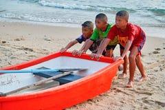 THAILAND PHUKET 18 MAART 2018 - Drie kinderen die een vissersboot duwen aan kust Concept kinderarbeid van de inboorling stock afbeelding