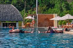 THAILAND, PHUKET, MARCH 22, 2018 - two men are resting lying in the outdoor pool. Copy space Stock Photos