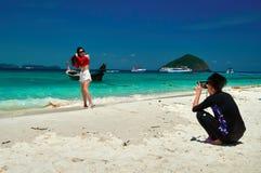 THAILAND PHUKET, 19 MARS 2018 - den unga mannen tar foto på smartphoneflicka på den tropiska stranden, under havsfjärden Unga kin Arkivfoton