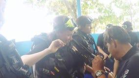 Thailand, Phuket, 30 november 2015. Man training helps girls wearing diving suit, preparing for dive. 1920x1080 stock footage