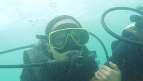 Thailand, Phuket, 30 november 2015. Young woman diving with her dive trainer in stunning crystal clear lagoon on exotic stock video footage