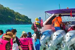 THAILAND, RACHA YAI ISLAND, MARCH 19, 2018 - passengers with children in lifejackets get on the speedboat. THAILAND, RACHA YAI ISLAND, MARCH 19, 2018 royalty free stock images