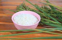 Thailand rice on wooden floor,Thailand rice onto a wooden spike. Thailand rice, white rice on a wooden floor,White rice on a wooden spike,Cup of rice on Stock Photo