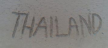 `-Thailand ` som är skriftlig i sanden på stranden Royaltyfri Bild