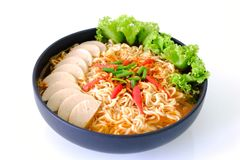 Thailand Spicy Instant noodle soup on white background. Spicy Instant noodle soup with fermented pork sausage and vegetables in a black bowl on white background Royalty Free Stock Photo