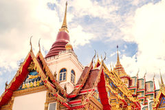 Thailand tempel på en molnig himmel med solen Arkivfoto
